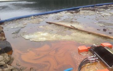 Удержание боновыми заграждениями загрязненного льда и нефтесодержащей эмульсии на водной поверхности