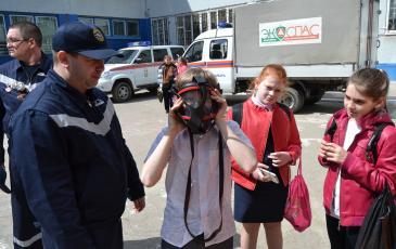 Заместитель начальника ПАСФ Самарского центра «ЭКОСПАС» Журавчак И.Н. помогает детям примерить дыхательный аппарат