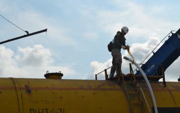 Спасатель «ЭКОСПАС» в костюме химической защиты готовит перекачку содержимого цистерны в ёмкость временного хранения