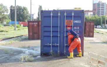 Спасатель «ЭКОСПАС» в газозащитном костюме открывает контейнер