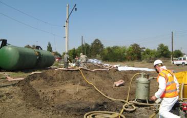 Спасатели «ЭКОСПАС» в костюмах химической защиты проводят обработку сорбентом места разлива