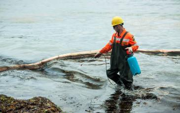 Спасатель «ЭКОСПАС» при очистке береговой полосы загрязненной бухты